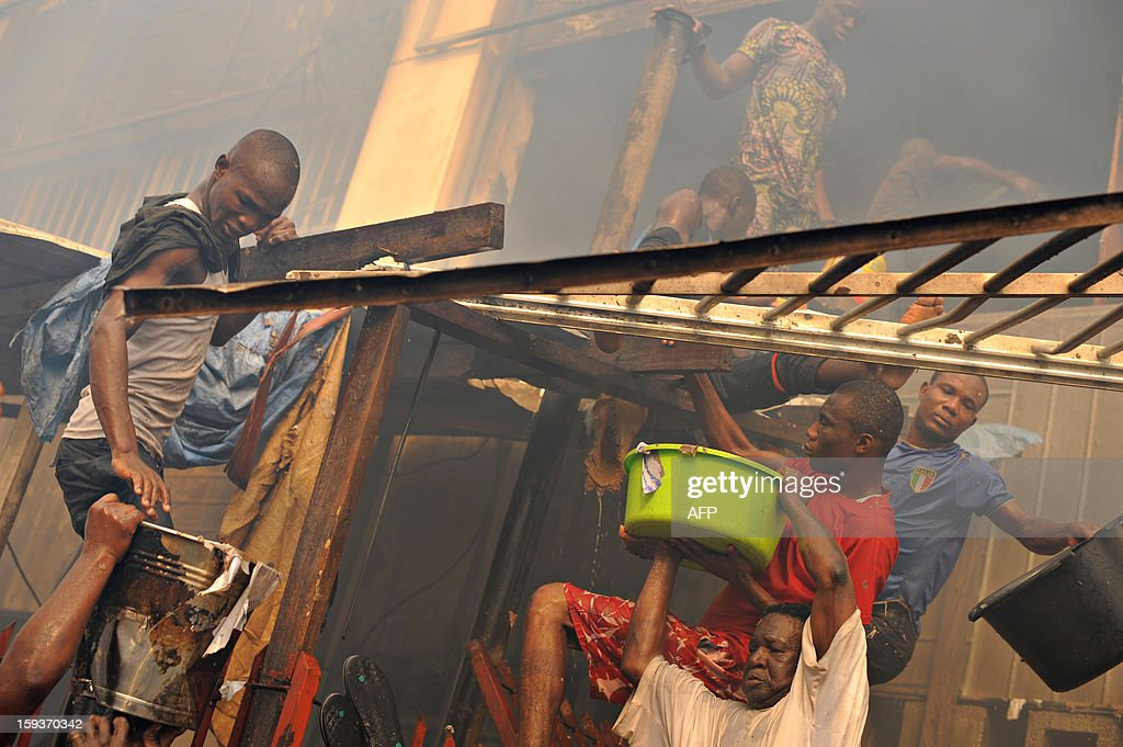 People use buckets of water to assist firefighters in extinguishing the blaze in Lome's Grand Marche (''Big Market'') on January 12, 2013 in Lome. The market was engulfed in flames late on January 11, 2013. AFP Photo / Daniel Hayduk