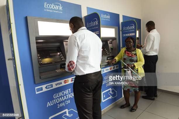 People use Ecobank Ivory Coast cash dispensers on September 18 2017 in Abidjan EcobankIvory Coast the Ivorian subsidiary of panAfrican bank Ecobank...