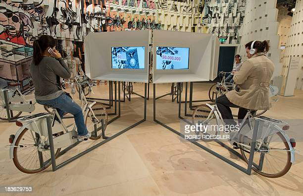 People use generatorequipped bikes to play info videos at the booth of Brazil at the Frankfurt Book Fair 2013 on October 8 2013 in Frankfurt am Main...