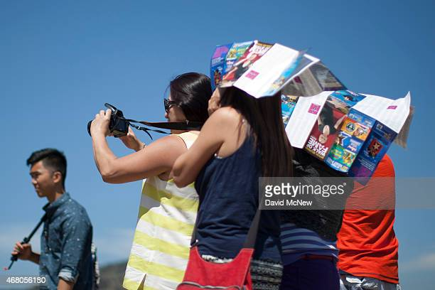 People use Hollywood tourist maps as makeshift sunshades as they photograph friends in Griffith Park on March 29 2015 in Los Angeles California A...