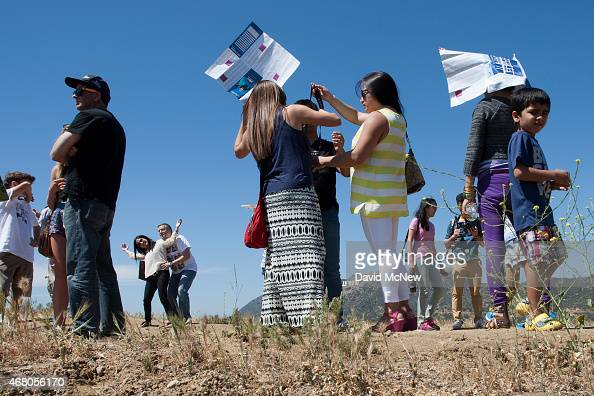 People use Hollywood tourist maps as makeshift sunshades as they photograph one another with the Hollywood Sign in the distance in Griffith Park on...