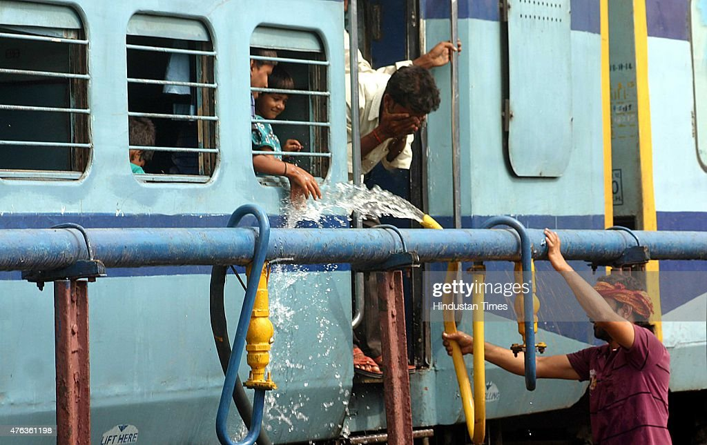 People use railway hose pipe to fill water bottles and cool themselves at the Bhopal railway station even as the day remained extremely hot and humid...