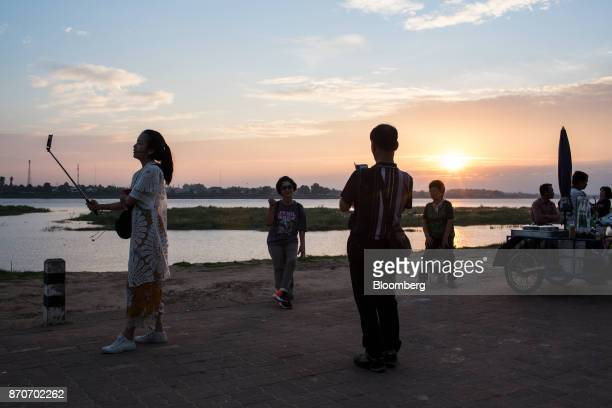 People use smartphone to take photographs on a promenade along the Mekong river in Vientiane Laos on Thursday Nov 2 2017 Located in the Mekong region...