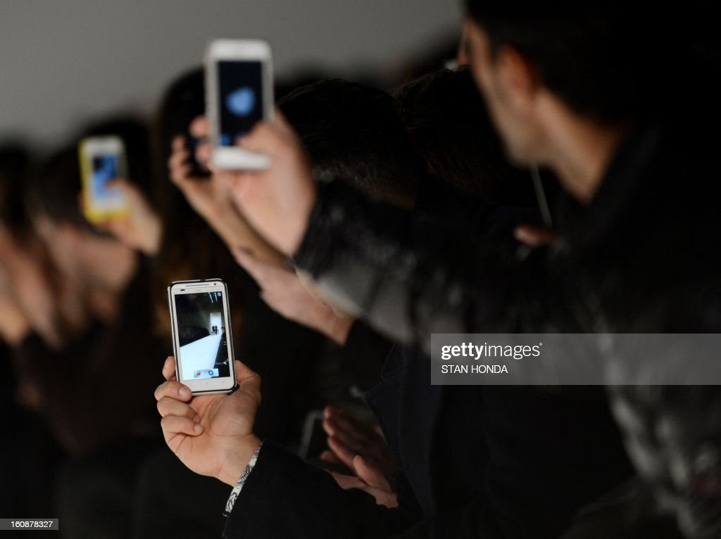 People use smartphones to photograph the Nicholas K show during the Mercedes-Benz Fashion Week Fall 2013 collections on February 7, 2013 in New York. AFP PHOTO/Stan HONDA