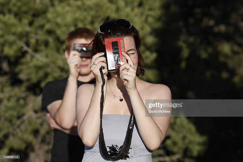 People use solar film to photograph the first annular eclipse seen in the U.S. since 1994 on May 20, 2012 in Grand Canyon National Park, Arizona. Differing from a total solar eclipse, the moon in an annular eclipse appears too small to cover the sun completely, leaving a ring of fire effect around the moon. The eclipse is casting a shallow path crossing the West from west Texas to Oregon then arcing across the northern Pacific Ocean to Tokyo, Japan.