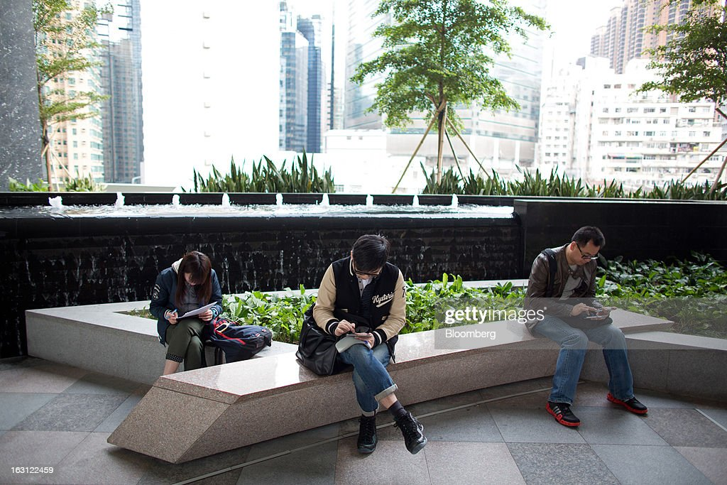 People use their mobile devices while sitting in the Sky Garden at Hysan Development Co.'s Hysan Place mall in the Causeway Bay district of Hong Kong, China, on Monday, March 4, 2013. Hysan is scheduled to release earnings on March 6. Photographer: Lam Yik Fei/Bloomberg via Getty Images