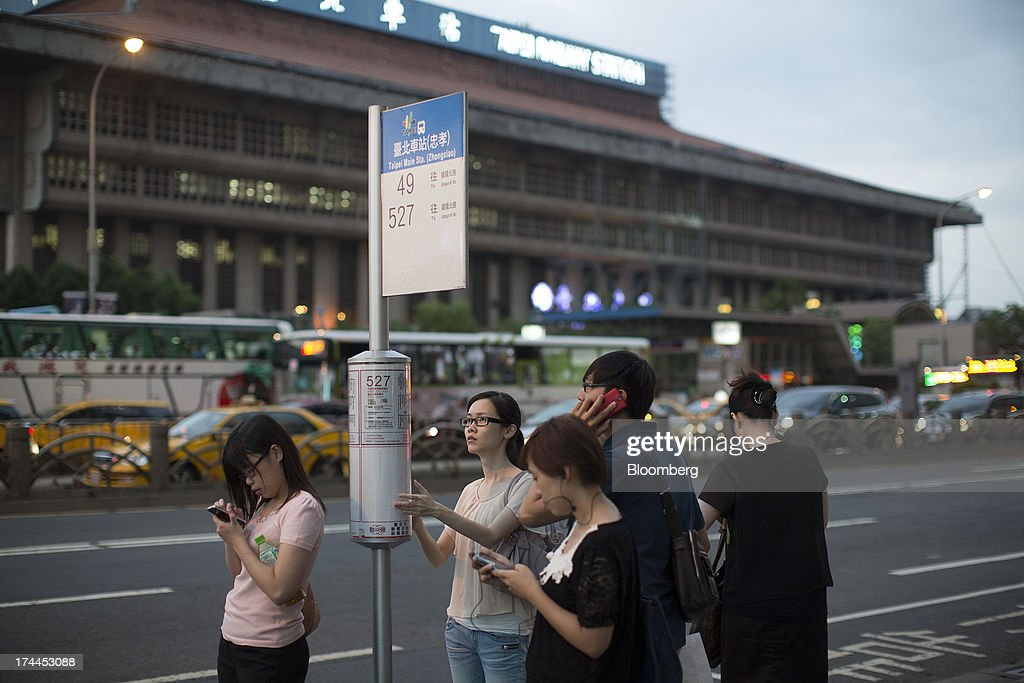 People use their mobile devices while they wait at a bus stop near Taipei Main Station in Taipei, Taiwan, on Wednesday, July 24, 2013. Taiwan President Ma Ying-jeou ruled out driving down the Taiwan dollar to boost exports following the currencys rally against the yen and said the government still aims for growth of at least 2 percent this year. Photographer: Jerome Favre/Bloomberg via Getty Images