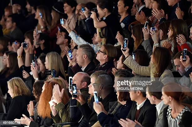 People use their mobile phones during the Miu Miu 2016 Spring/Summer readytowear collection fashion show on October 7 2015 in Paris / AFP / MIGUEL...