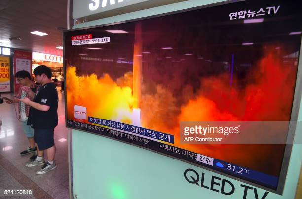 People use their mobile phones next to a television screen showing a video footage of North Korea's latest test launch of an intercontinental...