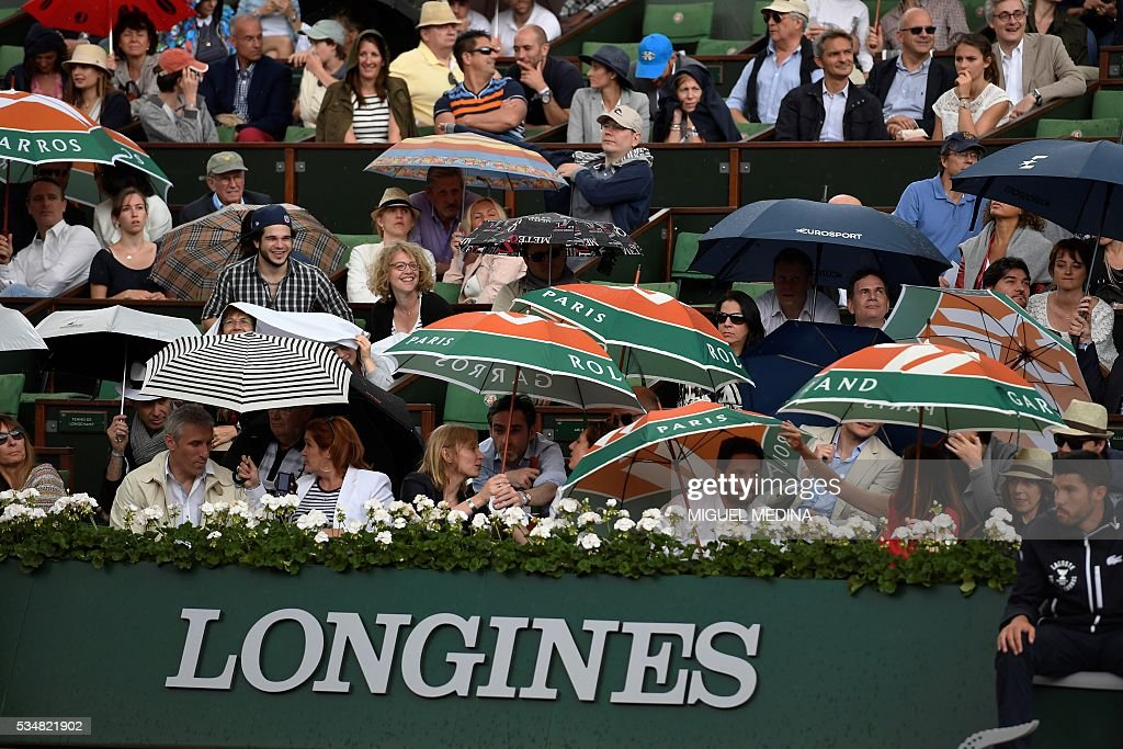 People use umbrella during the women's third round match between US Serena Williams and France's Kristina Mladenovic at the Roland Garros 2016 French Tennis Open in Paris on May 28, 2016. / AFP / MIGUEL