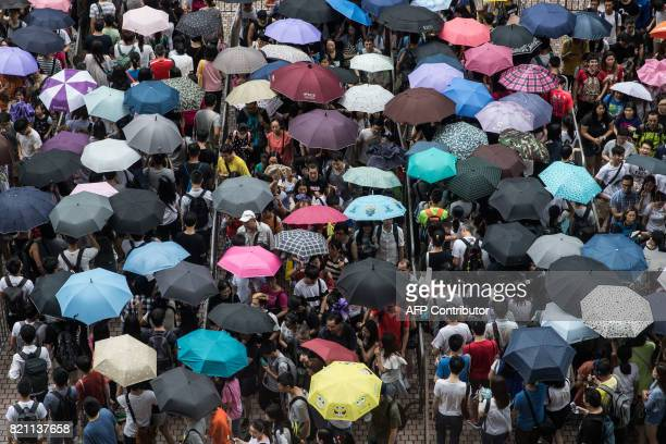 People use umbrellas to shelter from the rain as they queue to enter the International Book Fair in Hong Kong on July 23 2017 This year's book fair...
