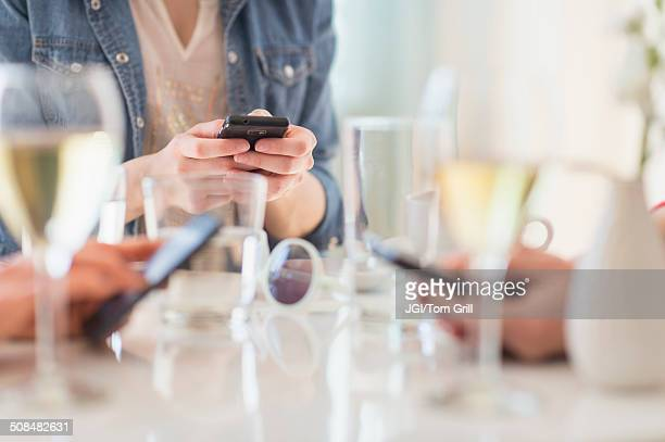 People using cell phones at dinner table