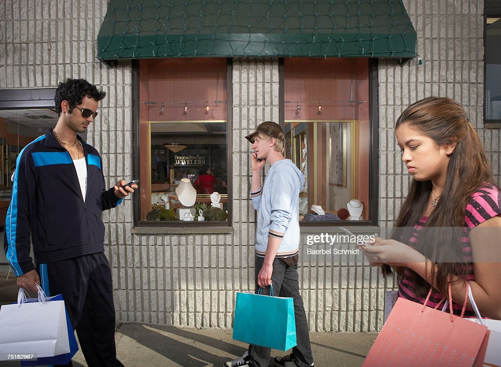 People using mobile phones while walking past jewellery store