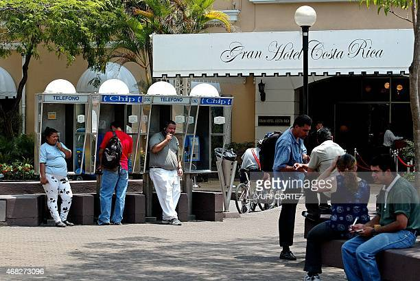 People using public phones in front of the Grand Hotel Costa Rica in San Jose Costa Rica 27 April 2005 AFP PHOTO/Yuri CORTEZ