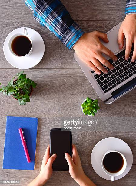 People using smartphone and laptop on desk