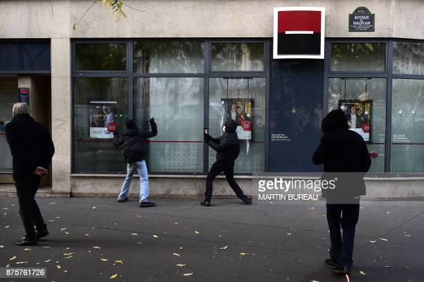 People vandilize a branch of the Societe Generale bank on the sideline of in a march dubbed 'marche sur l'Elysée' called by the Social Front against...