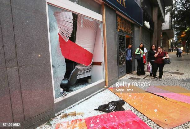 People view a bank window damaged by protestors during a nationwide general strike on April 28 2017 in Rio de Janeiro Brazil The general strike was...