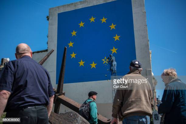 People view a recently painted mural by British graffiti artist Banksy depicting a workman chipping away at one of the stars on a European Union...