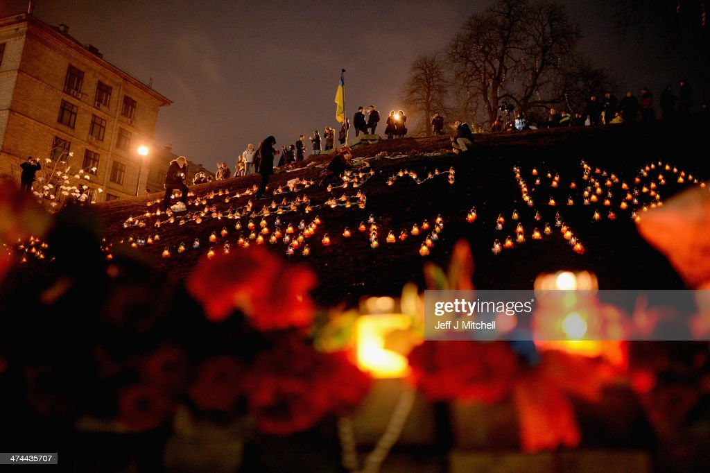 People view floral tributes to anti-government demonstrators killed in clashes with police in Independence Square on February 23, 2014 in Kiev, Ukraine.Prime Minister Yanukovych is said to have left Kiev for a eastern stronghold as the country's parliament voted to remove Yanukovych from office and call for new elections.