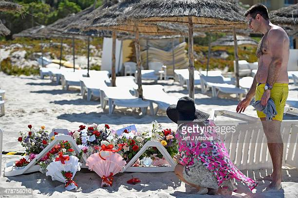 People view flowers placed at the beach next to the Imperial Marhaba Hotel where 38 people were killed yesterday in a terrorist attack on June 27...