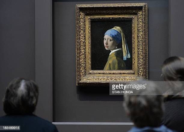 People view 'Girl with a Pearl Earring ' by Johannes Vermeer in the exhibition 'Vermeer Rembrandt and Hals Masterpieces of Dutch Painting from the...