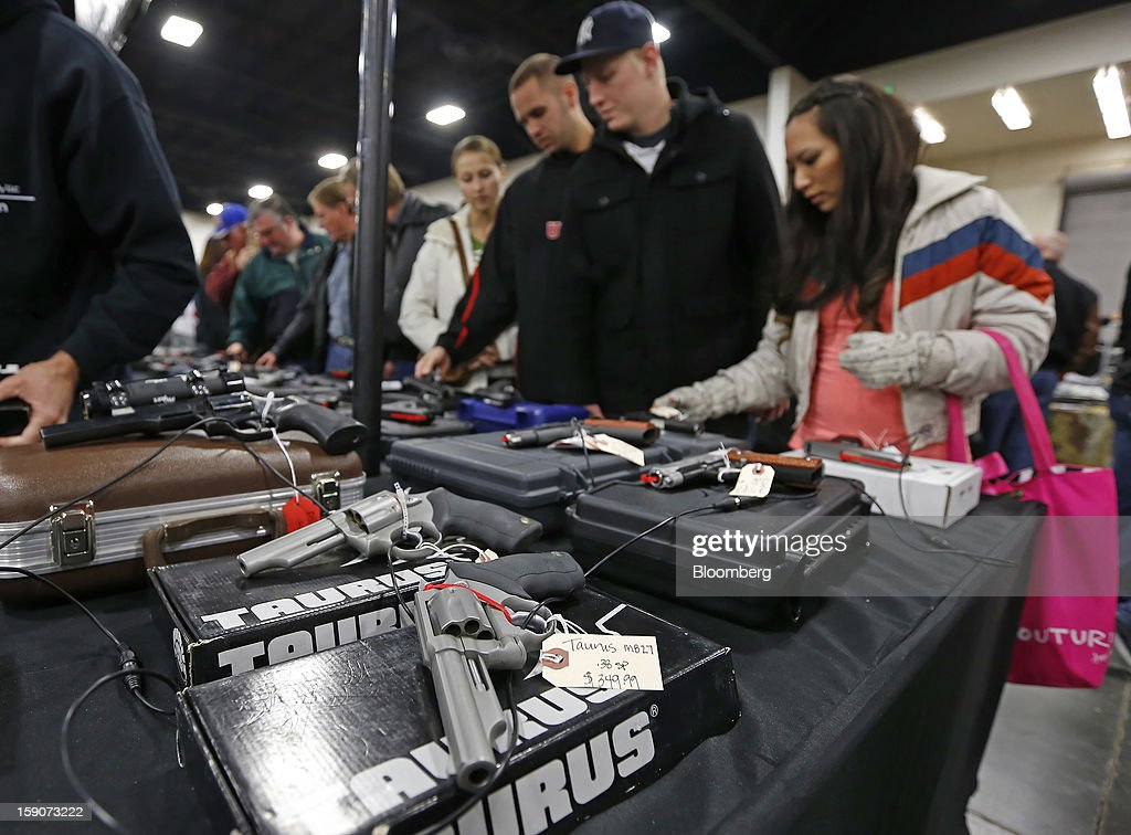 People view handguns including guns made by Taurus at the Rocky Mountain Gun Show in Sandy, Utah, U.S., on Saturday, Jan. 5, 2013. A working group led by Vice President Joe Biden is seriously considering measures that would require universal background checks for firearm buyers, track the movement and sale of weapons through a national database, strengthen mental health checks and stiffen penalties for carrying guns near schools or giving them to minors. Photographer: George Frey/Bloomberg via Getty Images