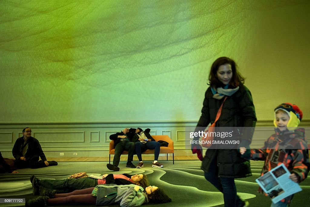 People view Janet Echelman's 1.8 on the ceiling at the Smithsonian's Renwick Gallery February 12, 2016 in Washington, DC. / AFP / Brendan Smialowski / RESTRICTED TO EDITORIAL USE - MANDATORY MENTION OF THE ARTIST UPON PUBLICATION - TO ILLUSTRATE THE EVENT AS SPECIFIED IN THE CAPTION