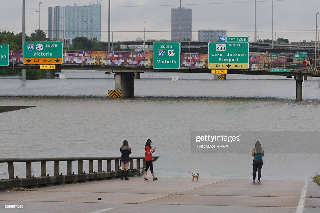 TOPSHOT - People view the flooded highways in Houston on August 27, 2017 as the city battles with tropical storm Harvey and resulting floods. Massive flooding unleashed by deadly monster storm Harvey left Houston -- the fourth-largest city in the United States -- increasingly isolated Sunday as its airports and highways shut down and residents fled homes waist-deep in water. / AFP PHOTO / Thomas B. Shea