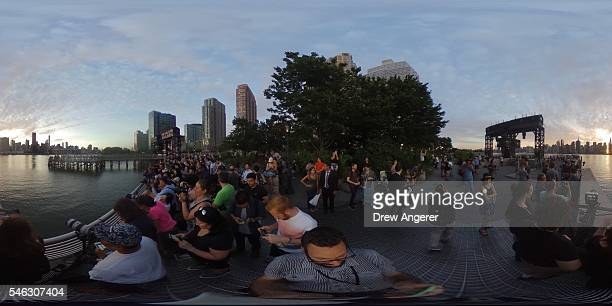 People view the 'Manhattanhenge' sunset from Hunters Point South Park July 11 2016 in the Queens borough of New York City 'Manhattanhenge' is created...