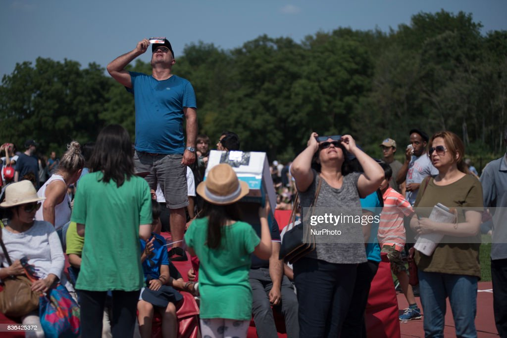 People view the partial solar eclipse in Toronto, Canada, on 21 August, 2017. Emotional sky-gazers stood transfixed across North America Monday as the Sun vanished behind the Moon in a rare total eclipse that swept the continent coast-to-coast for the first time in nearly a century.
