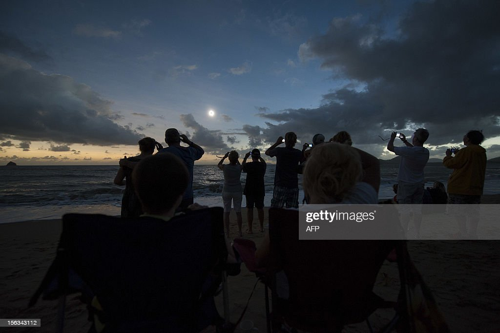 People view the solar eclipse from the beach at Palm Cove in Australia's Tropical North Queensland on November 14, 2012. Eclipse-hunters have flocked to Queensland's tropical northeast to watch the region's first total solar eclipse in 1,300 years on November 14, which occurred as the moon passed between the earth and the sun, casting a shadow path on the globe and lasting for a maximum on the Australian mainland of 2 minutes and 5 seconds. AFP PHOTO / Tourism Queensland == RESTRICTED TO EDITORIAL USE - MANDATORY CREDIT 'AFP PHOTO / AFP PHOTO / Tourism Queensland ' - NO