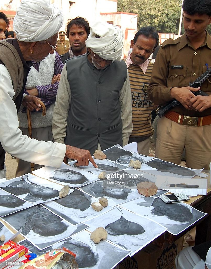 People viewing photographs of dead person to identify at the Allahabad Station.