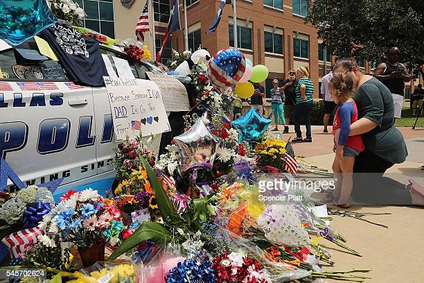 People visit a growing memorial at the Dallas police department's headquarters near the active crime scene in downtown Dallas following the deaths of...