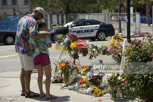People visit a makeshift memorial near the Emanuel AME Church June 18 2015 in Charleston South Carolina after a mass shooting at the Church on the...