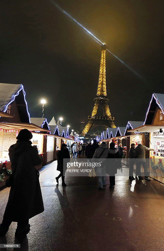 People visit a market in the 'Christmas village' during its inauguration on December 13, 2012, in Paris, as part of the 'Trocadero On Ice' event. An ice-skating rink also opened to public in front of the Eiffel tower, and will run until January 6, 2013. AFP PHOTO PIERRE VERDY