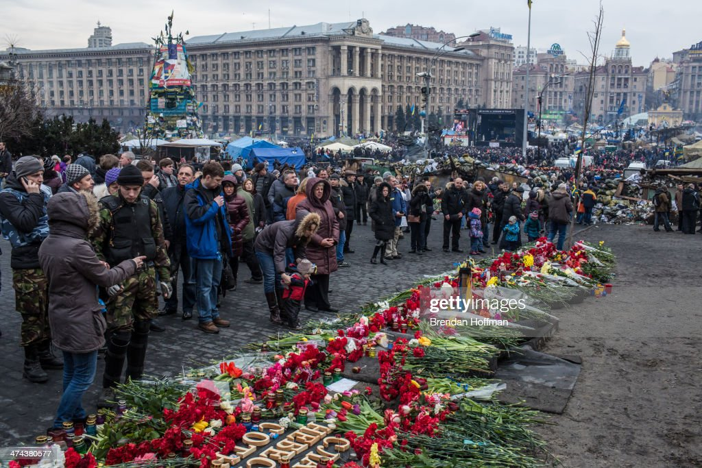 People visit a memorial to anti-government protesters killed in chashes with police on Independence Square on February 23, 2014 in Kiev, Ukraine. After a chaotic and violent week, Viktor Yanukovych has been ousted as President as the Ukrainian parliament moves forward with scheduling new elections and establishing a caretaker government.