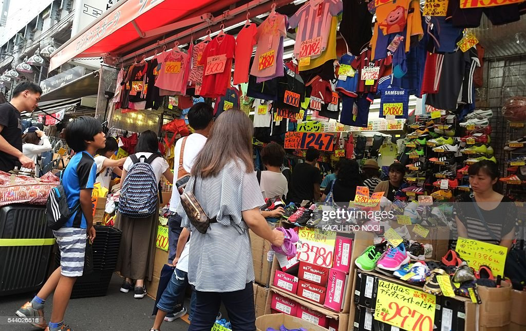 People visit a shop in Tokyo on July 1, 2016. Japan was clobbered with a one-two punch July 1 morning as weak data and a lacklustre business confidence report underscored the slowdown dragging on the world's number three economy. / AFP / KAZUHIRO