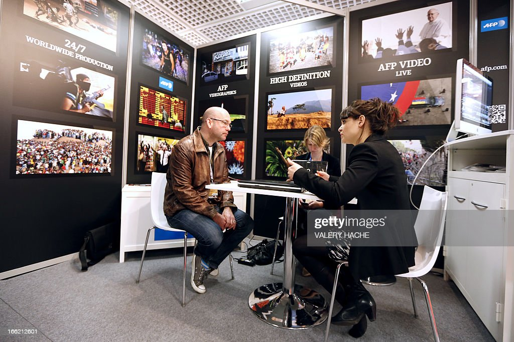 People visit AFP stand at the MIPTV one of the world's largest broadcasting and audio-visual trade show, on April 10, 2013 in Cannes, southeastern France . AFP PHOTO / VALERY HACHE