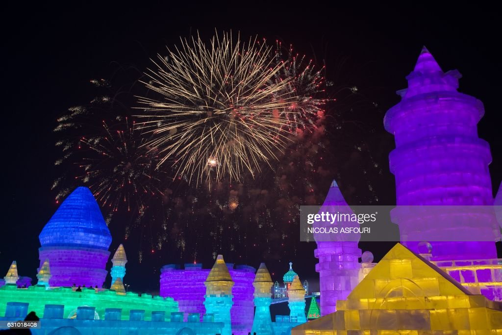 People visit ice sculptures illuminated by coloured lights as fireworks illuminate the night sky marking the opening of the Harbin Ice and Snow Festival to celebrate the new year in Harbin on January 5, 2017. / AFP / Nicolas ASFOURI