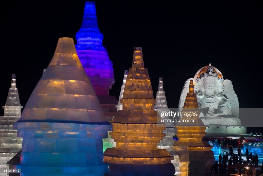 People visit ice sculptures illuminated by coloured lights at the Harbin Ice and Snow Festival to celebrate the new year in Harbin on January 5, 2017. / AFP / NICOLAS