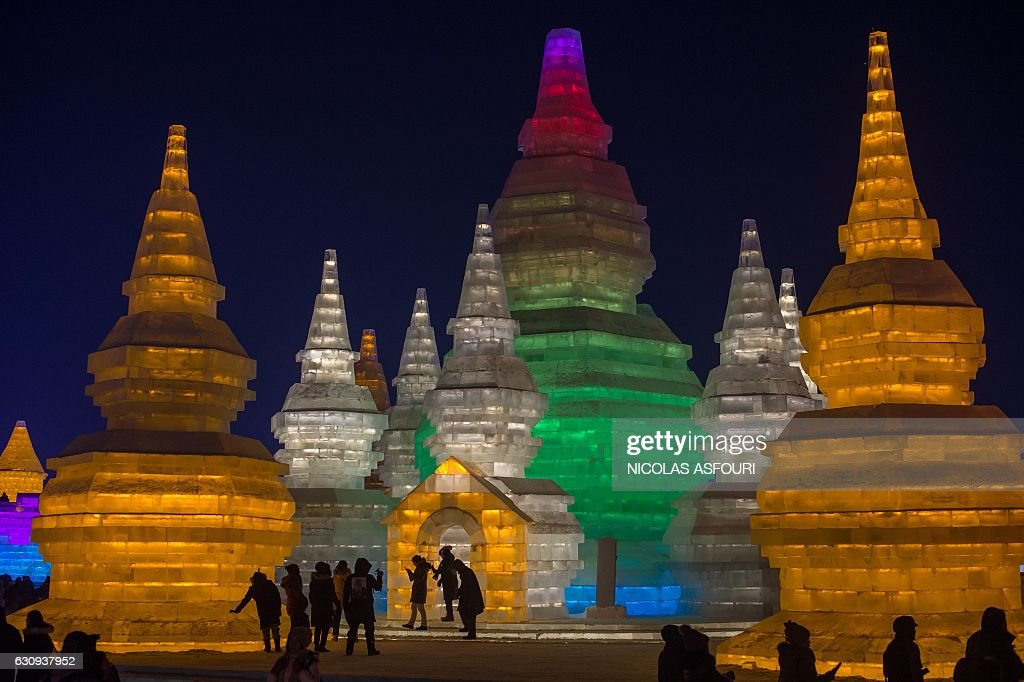 TOPSHOT - People visit ice sculptures illuminated by coloured lights at the Harbin Ice and Snow Festival to celebrate the new year in Harbin on January 4, 2017. / AFP / NICOLAS