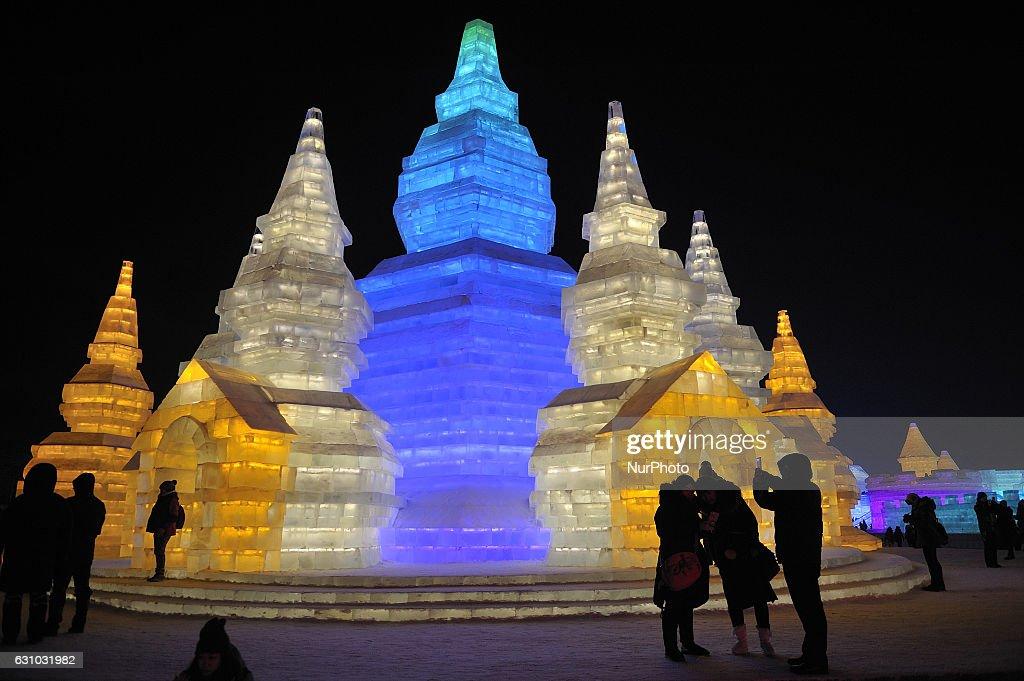 People visit ice sculptures illuminated by coloured lights at the Harbin Harbin Ice & Snow world to celebrate the 18th Harbin Ice & Snow world opening Ceremony in Harbin on January 5, 2017.