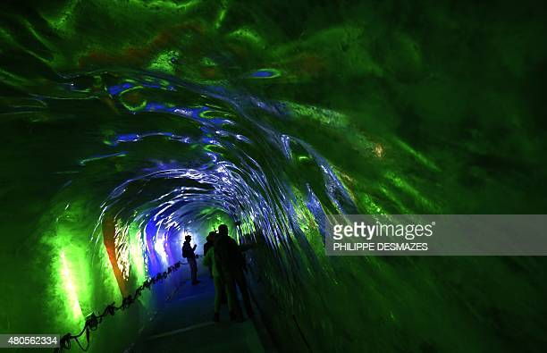 People visit 'La Grotte de glace' on June 8 2015 on the 'Mer de Glace' glacier in ChamonixMontBlanc French Alps At 7km long and 200m deep the Sea of...