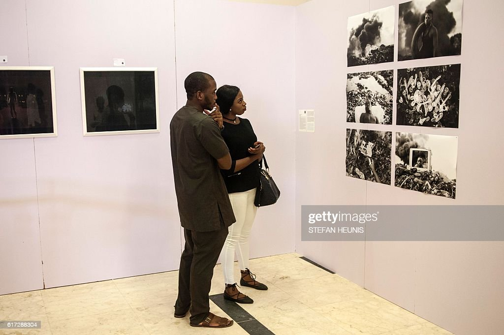 People visit photography expositions during the opening of the Lagos Photo festival in Lagos on October 22, 2016. Lagos Photo was launched in 2010 and is the first and only international arts festival of photography in Nigeria. / AFP / STEFAN