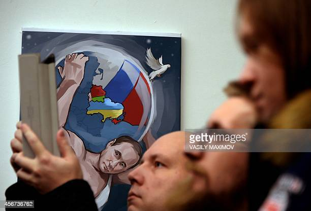 People visit the '12 Labors of Putin' art exhibition on October 6 marking the 62th birthday of Russia's President Vladimir Putin at the design...