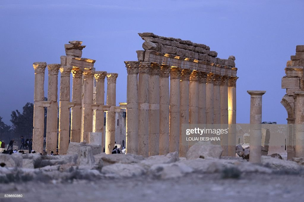 People visit the ancient historical site of Syria's ravaged Palmyra on May 6, 2016 following its recapture by regime forces from the Islamic State group fighter. Syrian troops backed by Russian air strikes and special forces on the ground recaptured UNESCO world heritage site Palmyra from Islamic State (IS) group fighters in March 2016. BESHARA