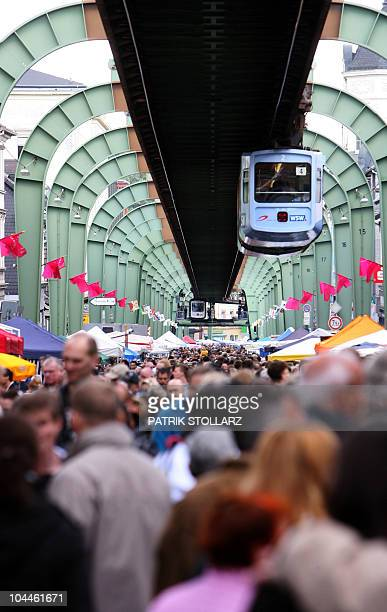 People visit the annual flea market in the Vohwinkel district near the city of Wuppertal western Germany as an elevated railway drives past on...