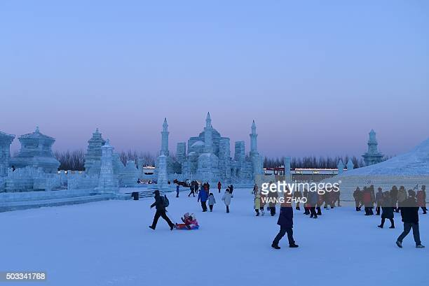 People visit the China Ice and Snow World on the eve of the opening ceremony of the Harbin International Ice and Snow Festival in Harbin northeast...