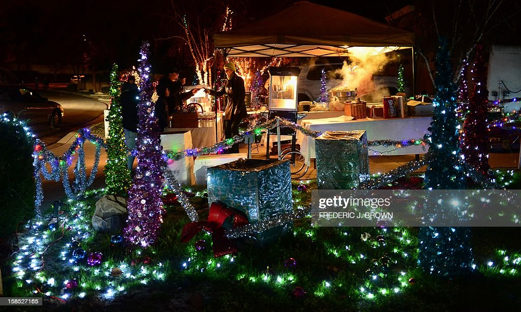 People visit the Christmas light decorations along Thoroughbred Lane in Rancho Cucamonga, forty plus miles east of downtown Los Angeles on December 17, 2012 in California, where for nearly a quarter of a century a normally quiet neighborhood for eleven months of the year comes alive with visitors to see the light displays from neighborhood residents, with some selling snacks and hot drinks in front of their homes. AFP PHOTO / Frederic J. BROWN