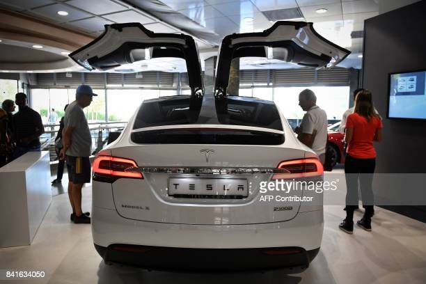People visit the electric carmaker Tesla showroom at El Corte Ingles store in Lisbon on September 1 2017 / AFP PHOTO / PATRICIA DE MELO MOREIRA